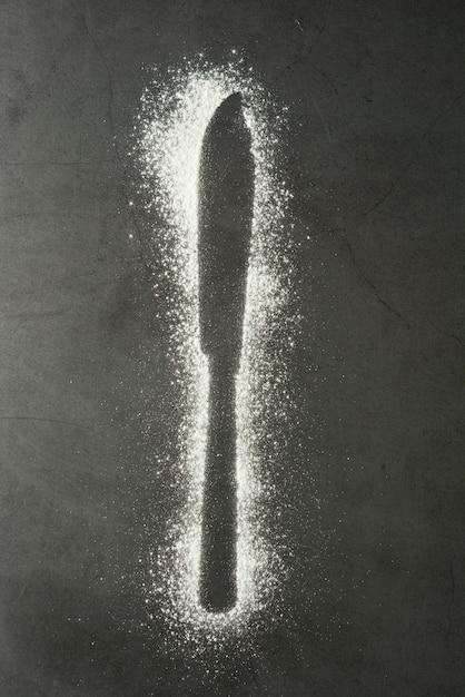 Silhouette de couteau faite de farine sur un fond noir Photo Premium