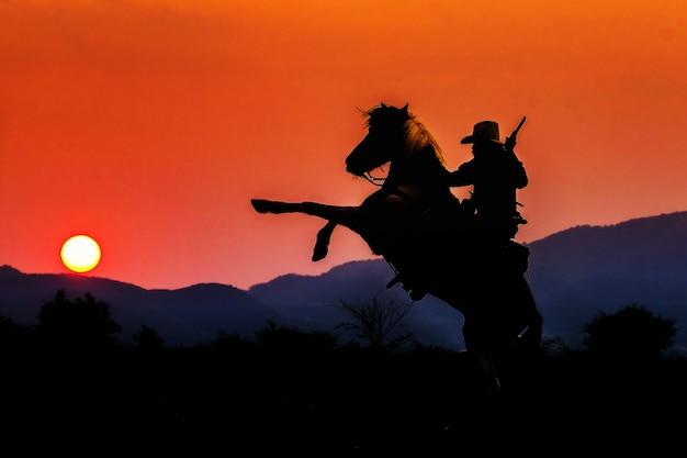 Silhouette de cow-boy sur un cheval au coucher du soleil Photo Premium