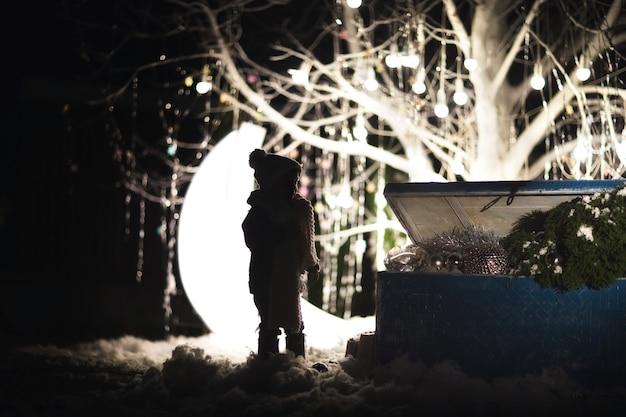La Silhouette Du Jeune Garçon En Vêtements D'hiver Près De L'ancien Coffre Bleu Avec Des Jouets Et Des Arbres Contre Noël Photo Premium
