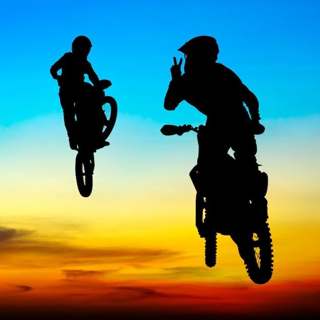 Silhouette du motocross cavalier sauter dans le ciel au coucher du soleil Photo Premium