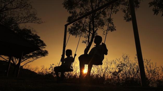 Silhouette enfants garçon et fille bénéficiant d'une belle journée ensoleillée jouant en arrière-plan Photo Premium