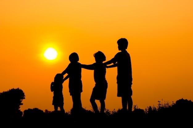 Silhouette d'enfants jouant avec coucher de soleil Photo Premium