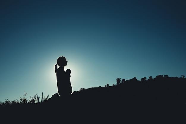 Silhouette de femme asiatique est prier sur la montagne Photo Premium