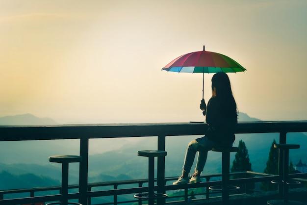 Silhouette De Femme Assise Sur Une Chaise Avec Un Parapluie Coloré à La Recherche De Brouillard Dans Les Montagnes Avec Un Ciel Dramatique Au Lever Du Soleil. Style Rétro Et Vintage Photo Premium