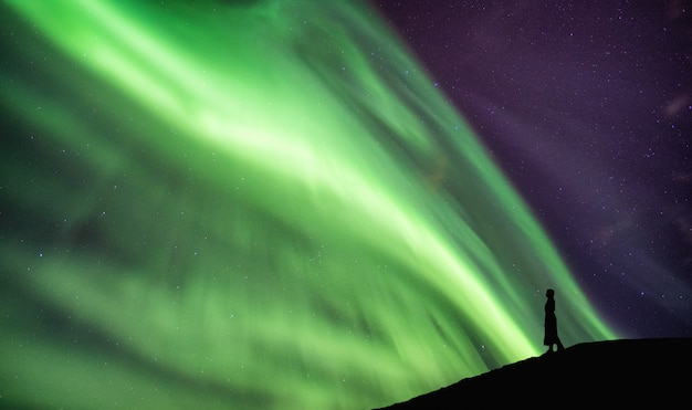 Silhouette femme debout sur la falaise avec aurores boréales danse sur ciel Photo Premium