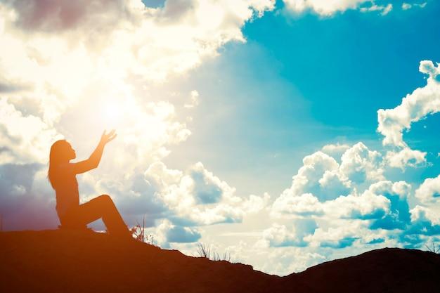 Silhouette de femme avec les mains levées Photo gratuit