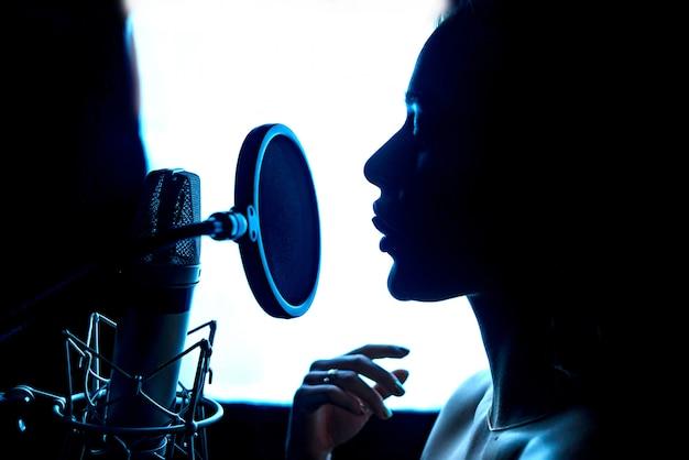 Silhouette de femme passionnée par la musique et le microphone dans le studio professionnel. chanteur devant un micro. fermer. Photo Premium