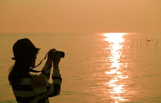 Silhouette d'une femme prenant des photos au soleil levant bord de mer Photo Premium