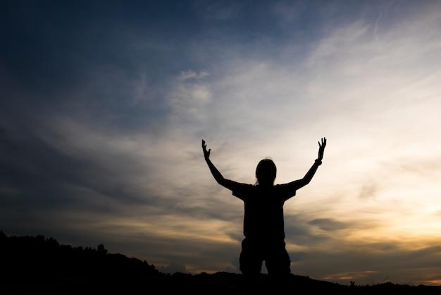 Silhouette de femme priant avec dieu Photo gratuit