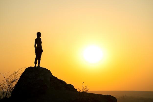 Silhouette D'une Femme Randonneur Debout Seul Sur Une Grosse Pierre Au Coucher Du Soleil Dans Les Montagnes. Touriste Sur Haut Rocher Dans La Nature Du Soir. Photo Premium