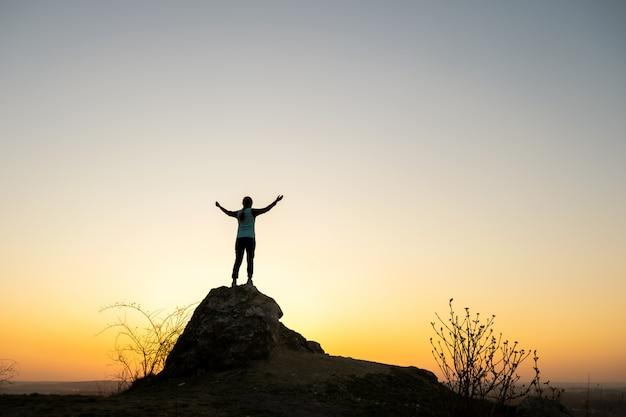 Silhouette D'une Femme Randonneur Debout Seul Sur Une Grosse Pierre Au Coucher Du Soleil Dans Les Montagnes. Touriste Levant Les Mains Sur Un Rocher élevé Dans La Nature Du Soir. Concept De Tourisme, De Voyage Et De Mode De Vie Sain. Photo Premium