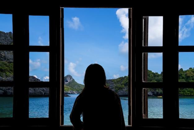 La silhouette d'une femme regardant par la fenêtre avec vue sur la mer. Photo Premium