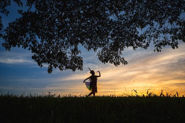 Silhouette Femmes Manohra Dansent Et Arbre Avec Coucher De Soleil Dans Le Sud De La Thaïlande. Photo Premium