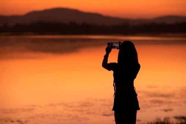 Silhouette Fille Asiatique Prenant Une Photo De Son Téléphone Portable à Des Attractions Touristiques Au Coucher Du Soleil, Sakonnakhon, Thaïlande. Photo Premium