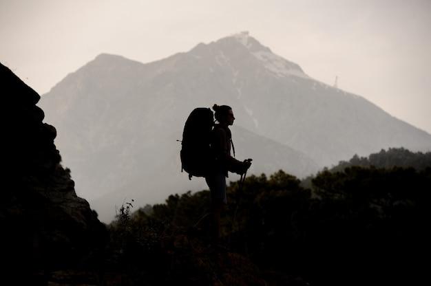 Silhouette fille marchant sur le rocher avec sac à dos et bâtons de randonnée Photo Premium