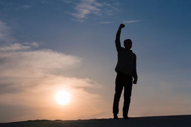 Silhouette De Gars Avec Les Mains Au Coucher Du Soleil Sur Le Ciel Photo Premium