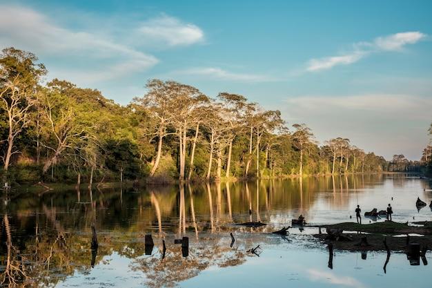 Silhouette de gens pêchant dans la rivière et la forêt au crépuscule Photo gratuit