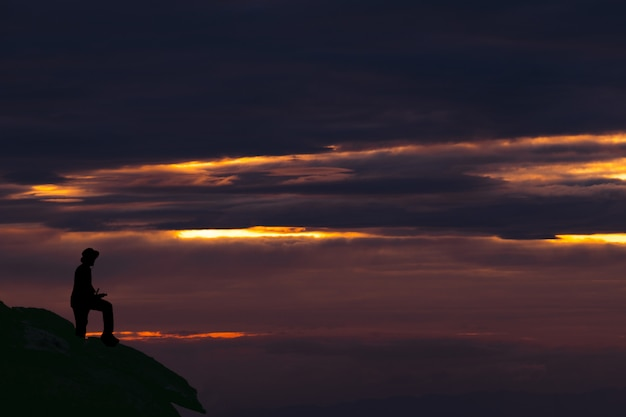 Silhouette homme debout sur la montagne contre le ciel au coucher du soleil Photo Premium