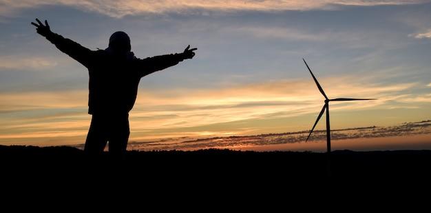 Silhouette homme heureux avec les mains vers le haut et éolienne au lever du soleil. Photo Premium