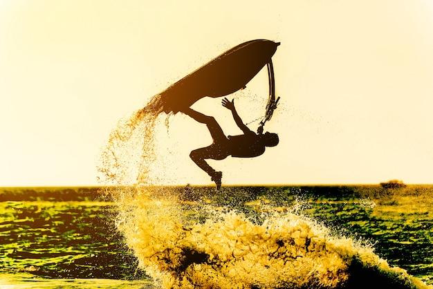 Silhouette de l'homme en jet ski freestyle au coucher du soleil. cavalier professionnel faire des tours en mer. Photo Premium