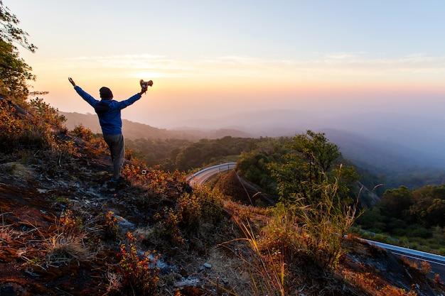 Silhouette de l'homme lever les mains au sommet de la montagne Photo Premium
