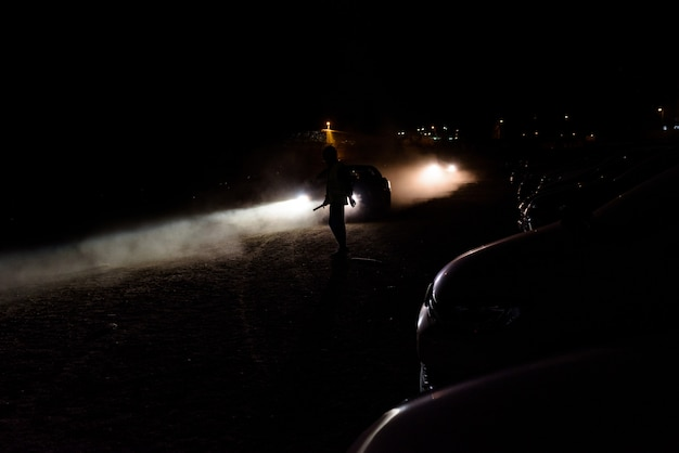 Silhouette d'homme méconnaissable illuminé par les phares d'une voiture dans une nuit sombre. Photo Premium
