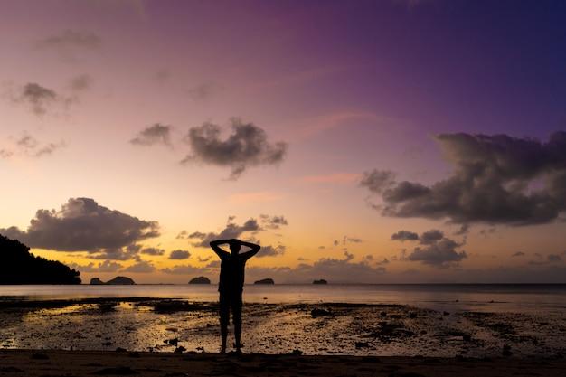 Silhouette D'un Homme Sur La Plage Au Coucher Du Soleil. L'homme Se Réjouit Rencontre Le Coucher Du Soleil Photo Premium