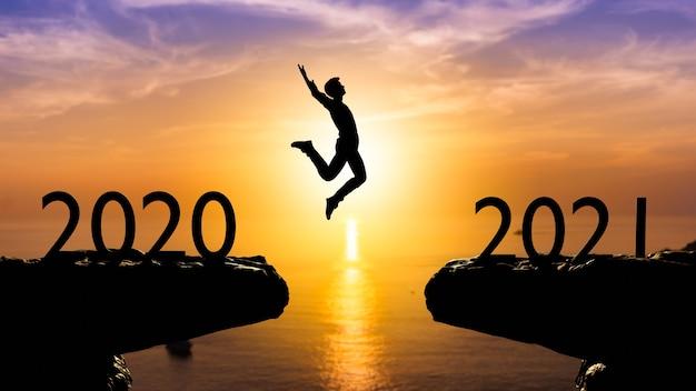 Silhouette Homme Saute Entre 2020 Et 2021 Ans Avec Mur De Coucher De Soleil, Concept De L'année 2021 Photo Premium
