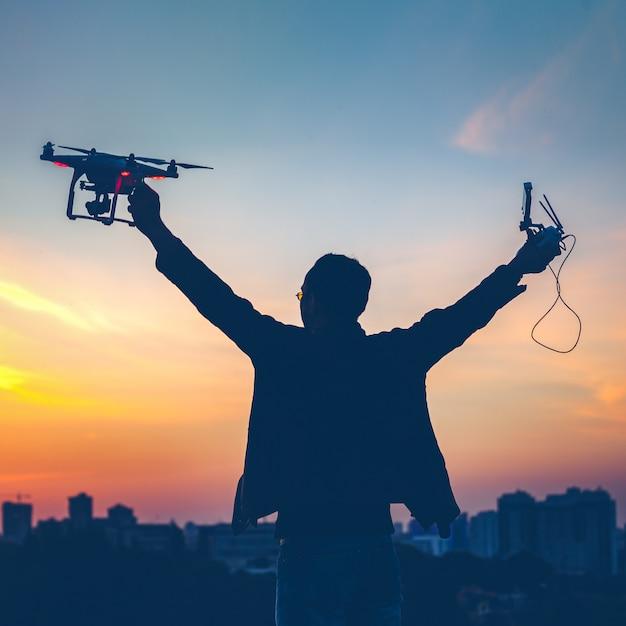 Silhouette D'homme Tenant Allumé Drone Photo Premium