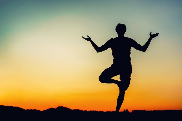 Silhouette d'homme en yoga pose au coucher du soleil Photo Premium