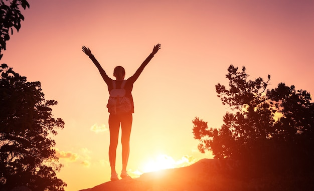 Silhouette D'une Jeune Femme Heureuse Dans Les Montagnes Au Coucher Du Soleil Photo Premium