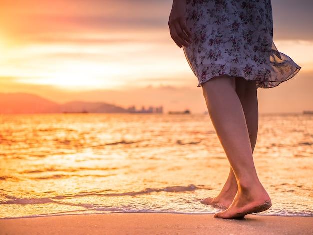 Silhouette de jeune femme marchant seule sur la plage au coucher du soleil Photo Premium