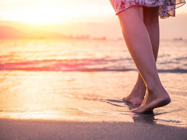 Silhouette de jeune femme marchant seule sur la plage au coucher du soleil. Photo Premium