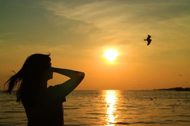 Silhouette de jeune femme en regardant le soleil levant sur un ciel doré avec un oiseau en vol Photo Premium