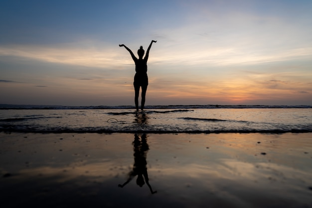 Silhouette D'une Jeune Fille Debout Dans L'eau Avec Ses Bras Levés Et Son Reflet Dans L'eau Photo gratuit