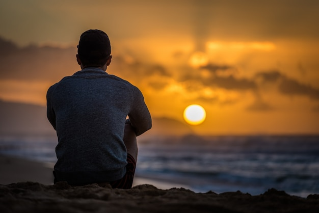 Silhouette de jeune homme caucasien assis sur sunset beach Photo Premium