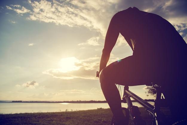 Silhouette jeune homme du cyclisme sur fond de coucher de soleil Photo Premium