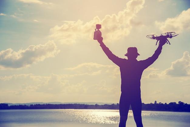 Silhouette D'un Jeune Homme Jouant Avec Le Drone Au Coucher Du Soleil Photo Premium