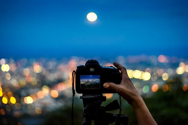 Silhouette De La Main Prenant Une Photo Avec Un Appareil Photo Reflex Numérique Sur Trépied Dans La Ville Lumière De Nuit Des Montagnes Photo Premium