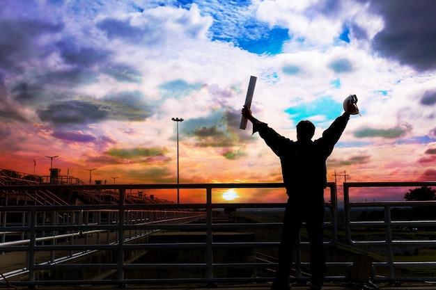 La silhouette masculine d'un ingénieur ravi par l'heure d'arrivée au coucher du soleil. Photo Premium