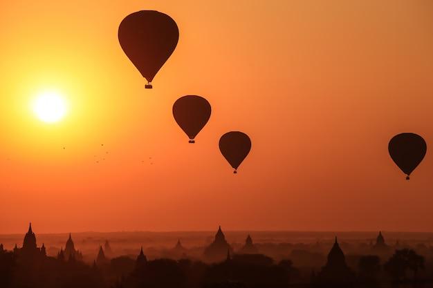 Silhouette, de, montgolfière, sur, bagan, à, levers de soleil, matin brumeux, myanmar Photo Premium