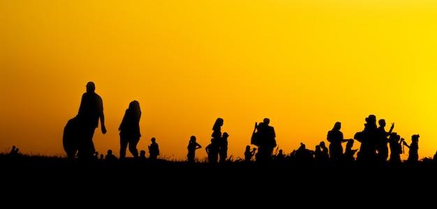 Silhouette de nombreux touristes prennent des photos par téléphone intelligent au sommet de la montagne pendant les heures du coucher du soleil. Photo Premium