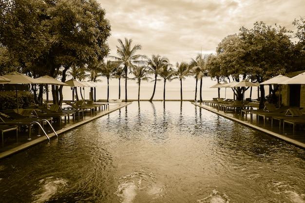 Silhouette de palmier sur la plage avec piscine Photo gratuit
