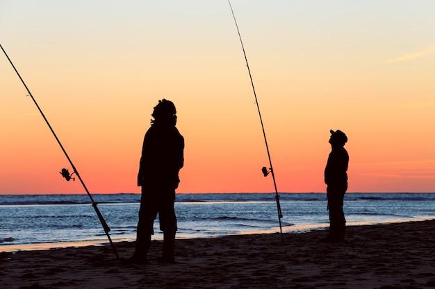 Silhouette Des Pêcheurs Sur La Plage Au Lever Du Soleil Photo Premium