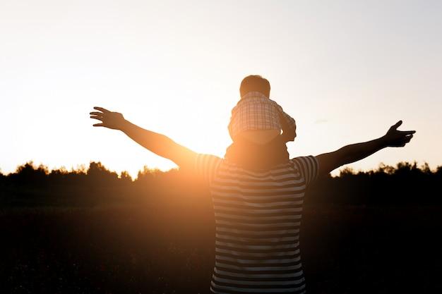 Silhouette père et fils marchant sur le terrain au coucher du soleil, garçon assis sur les épaules de l'homme. co Photo gratuit