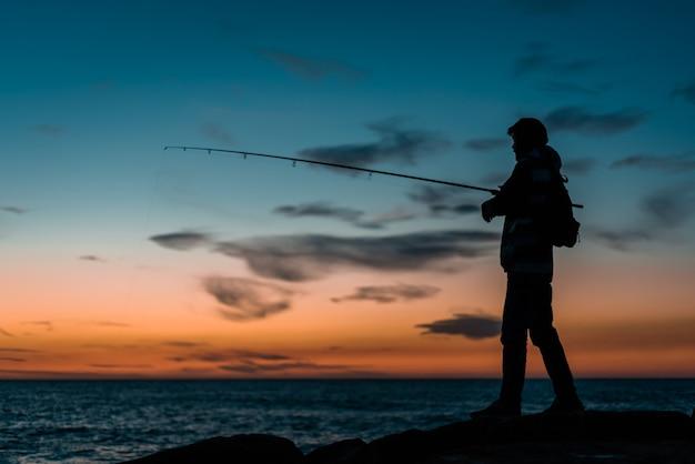 Silhouette De Personne Pêchant En Mer Photo gratuit