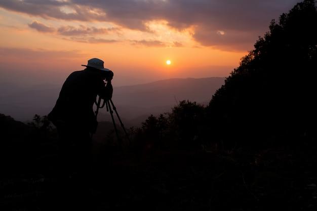 Silhouette d'un photographe qui tire un coucher de soleil dans les montagnes Photo gratuit