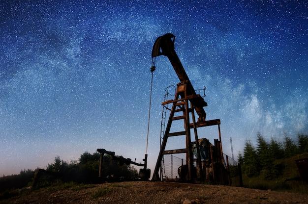 Silhouette de pompe à huile pompe le pétrole brut sur le champ pétrolifère dans la nuit sous le ciel étoilé. Photo Premium