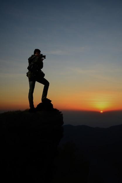 Silhouette sombre du photographe homme sur la falaise et la beauté du lever du soleil le matin. Photo Premium