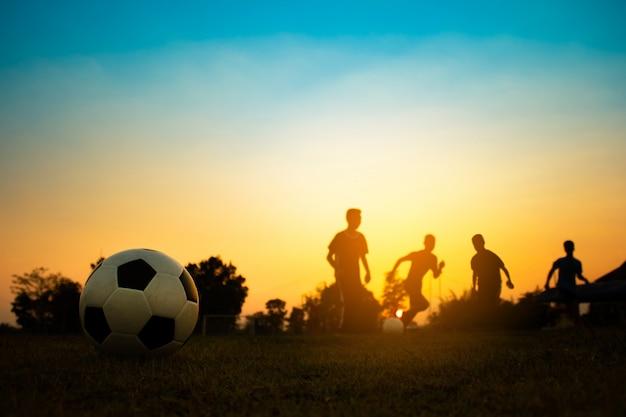 Silhouette de sport d'action en plein air d'un groupe d'enfants s'amusant à jouer au football Photo Premium